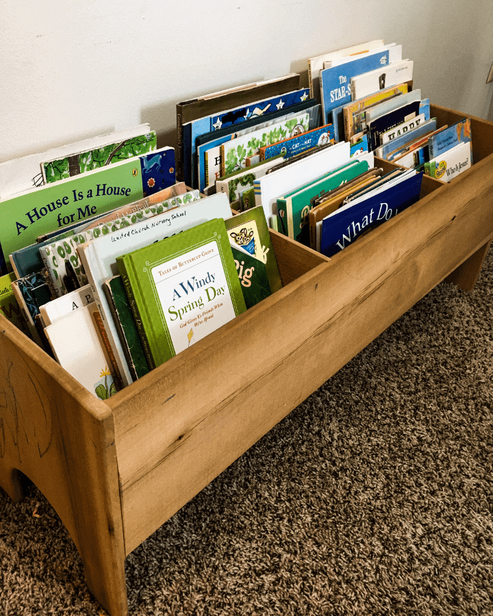Children's books in a book bin, purposefully placed there to create an educational atmosphere in the home.