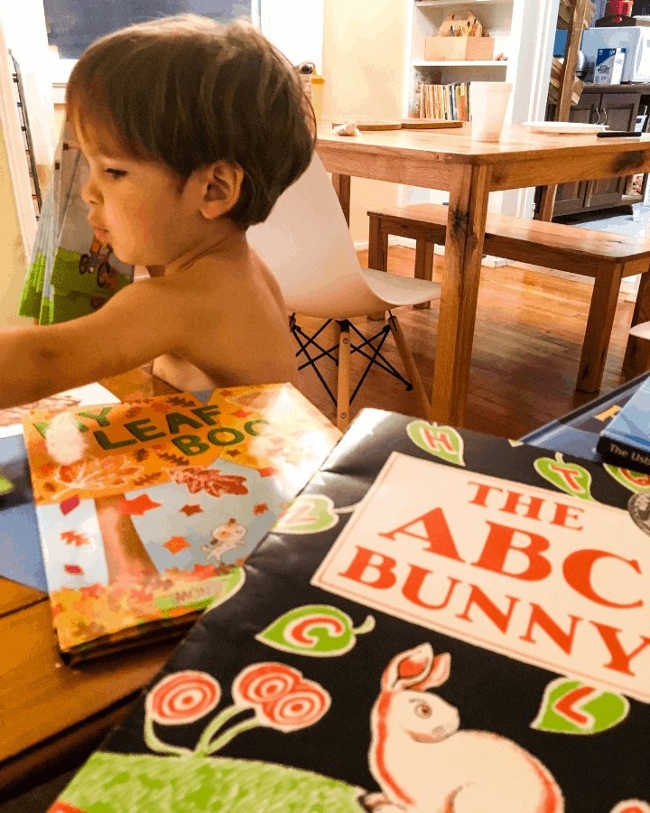 A boy looking at children's books on a side table.