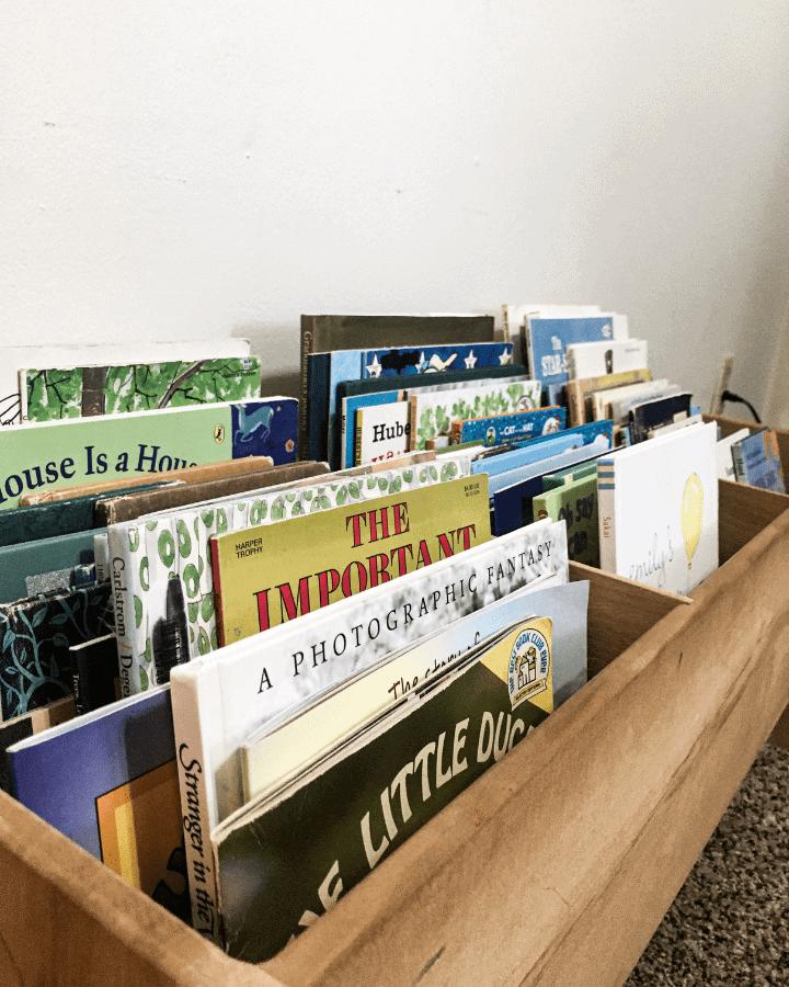 A close up of children's books in a book bin.