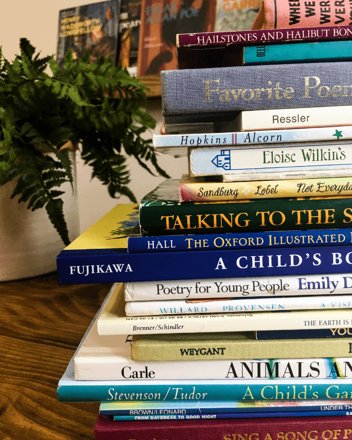 Tall stack of children's poetry books on a table