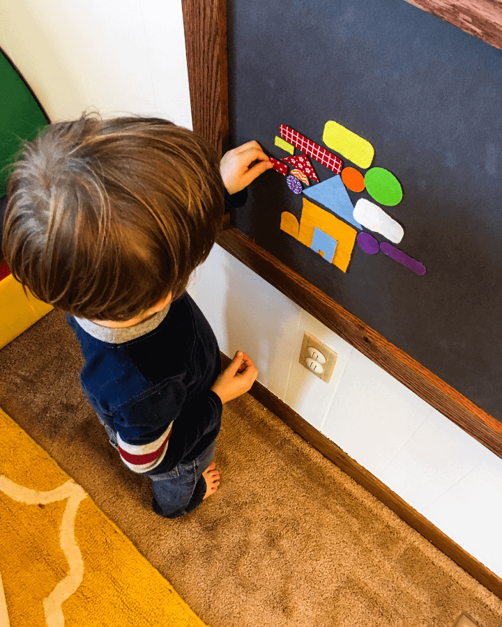 a boy playing with felt pieces during homeschool