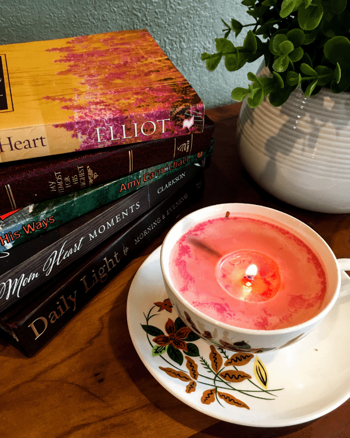 Five of the best devotionals for moms sitting on a table with a candle and a plant.