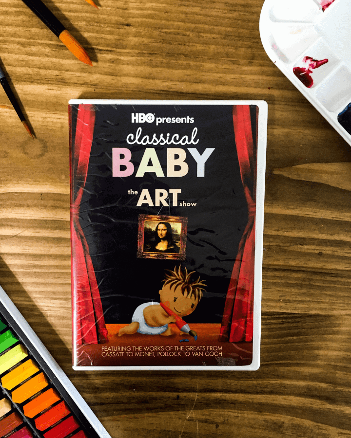 A Classical Baby Art Show DVD with art supplies surrounding it.