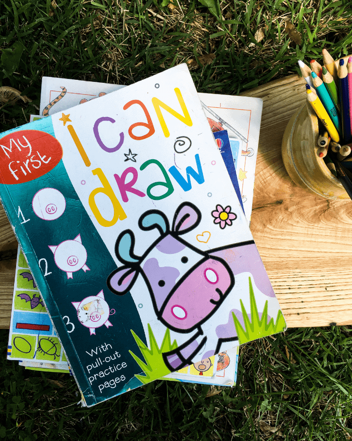 My First I Can Draw book on a piece of wood in the grass with colored pencils next to it.