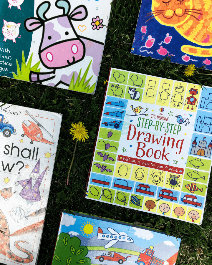 Five I Can Draw Books for Kids that are laid out on the grass with a dandelion.
