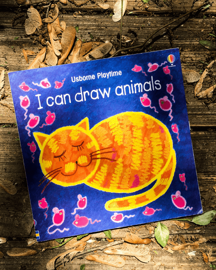A Drawing book with a cat on the front of it laying outside.