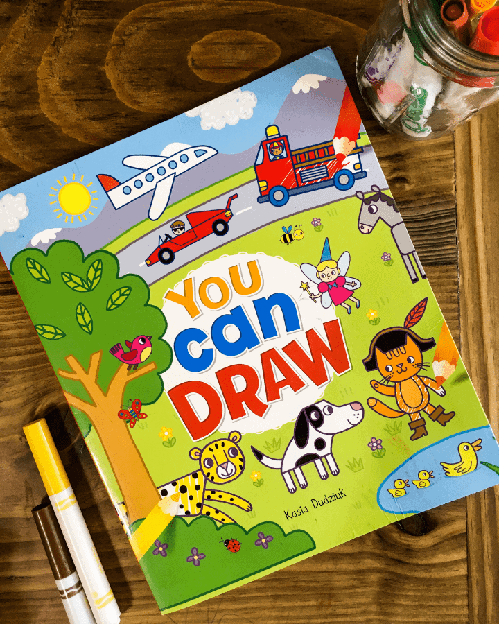 A kids You Can Draw book with markers surrounding it.