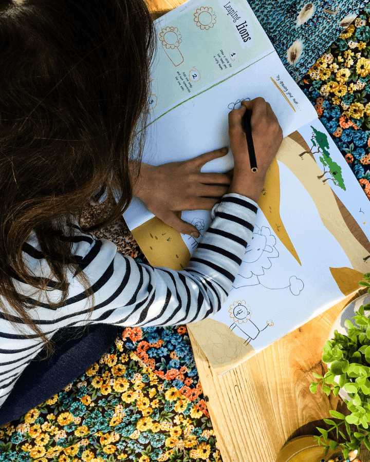 A girl drawing in a step by step drawing books for kids while laying on a blanket.