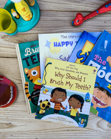 a stack of brushing teeth books for preschoolers next to tooth brushes