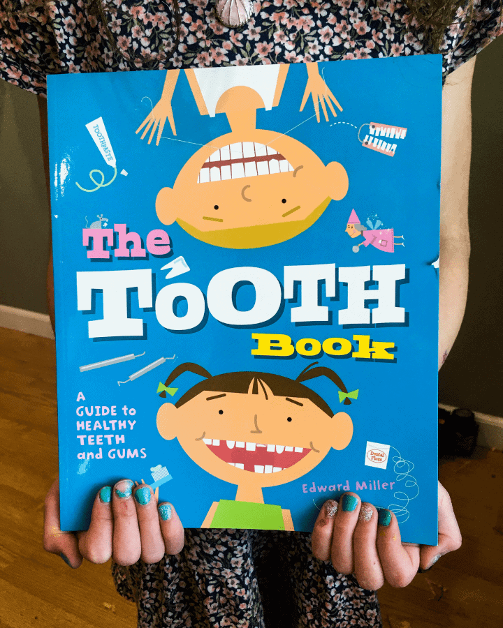 A girl holding a children's book about teeth.