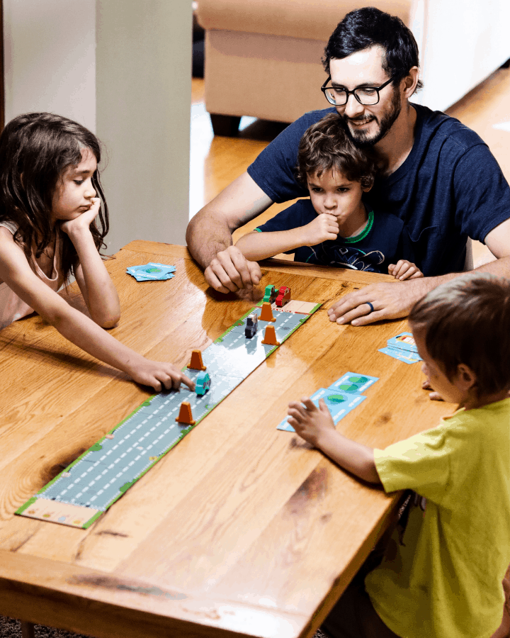 A dad playing a family board game at the table with his kids.
