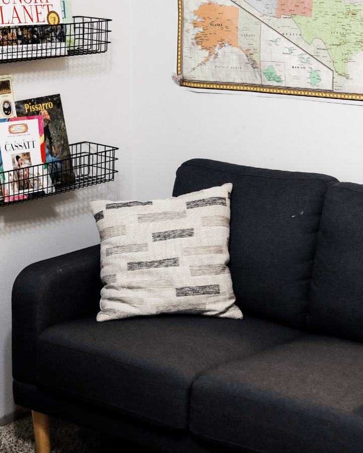A small couch, pillow and books on a wall shelf.  A cozy spot in an intentional home.