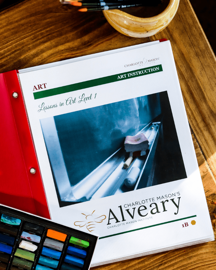 Charlotte Mason's Alveary Art Lessons Level for homeschool.  A notebook with the pages for the art lessons and chalk pastels sitting next to it, which are used during the course.