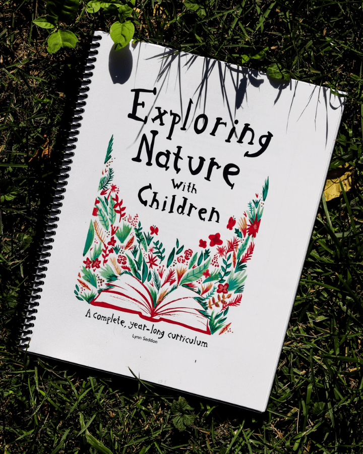 Exploring Nature with Children spiral notebook sitting on the grass for homeschool.